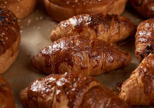Croissants assados em uma assadeira em papel vegetal, deliciosos e apetitosos pastéis