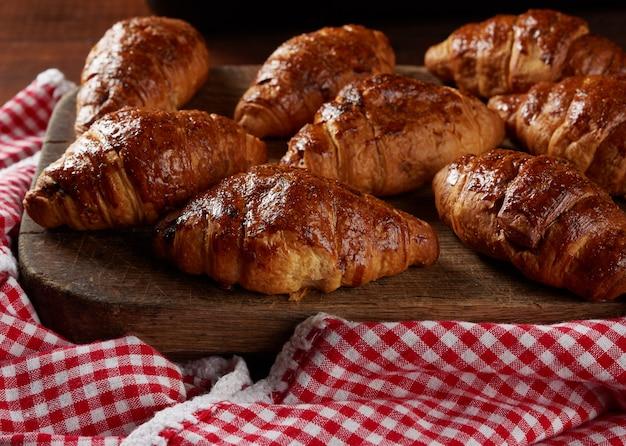 Croissants assados em uma tábua de madeira marrom, deliciosos e apetitosos pastéis