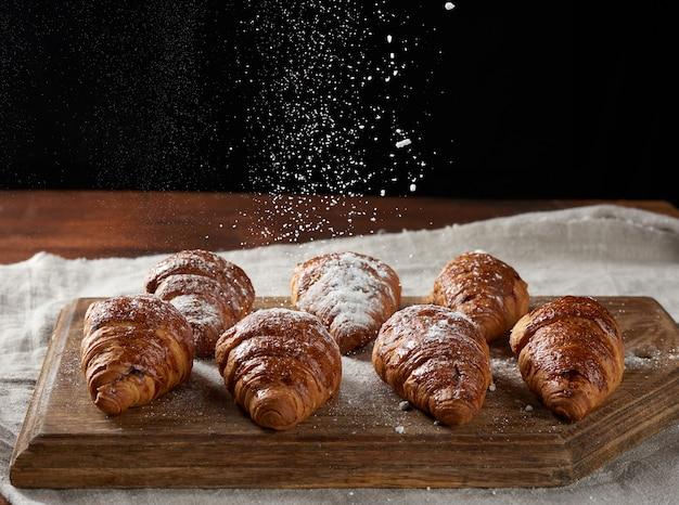 Croissants assados polvilhados com açúcar de confeiteiro em uma placa de madeira, o açúcar voa de cima