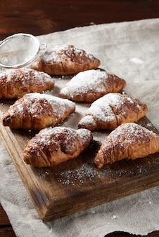 Croissants assados polvilhados com açúcar de confeiteiro repousam sobre uma placa de madeira marrom