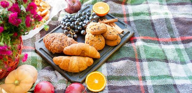 Croissants, biscoitos, uvas em uma placa nas folhas de outono amarelas. piquenique de outono no parque, um dia quente de outono. conceito de outono.