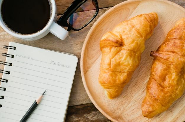 Croissants café caderno óculos lápis
