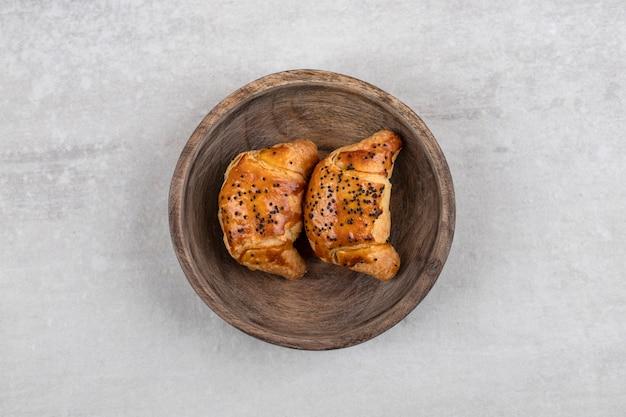 Croissants caseiros em uma placa, na mesa de mármore.