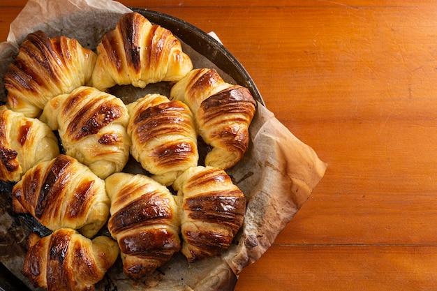 Croissants caseiros recém-assados, esfriando na assadeira. enquanto isso, as primeiras luzes da manhã entram pela janela