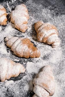 Croissants com açúcar em pó na mesa cinza.