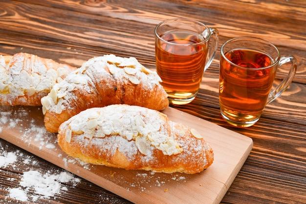 Croissants com amêndoas e chá em uma mesa de madeira.