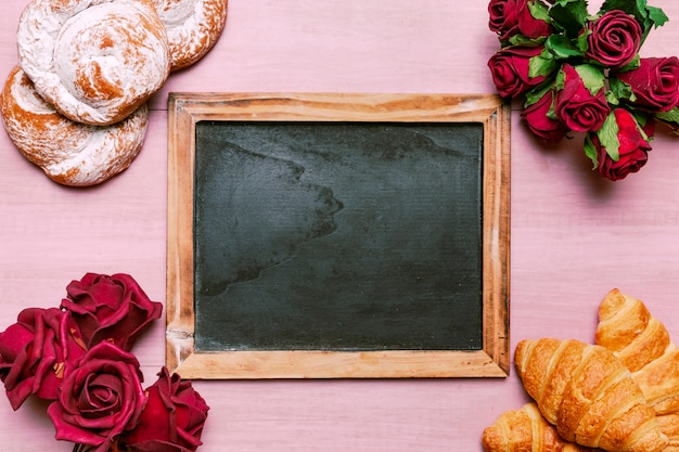 Croissants com bouquet de rosas vermelhas e lousa