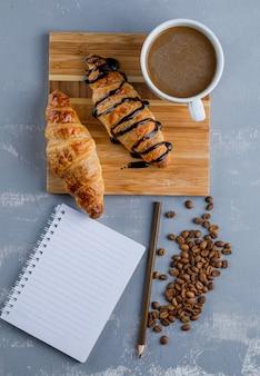 Croissants com café, caderno, lápis, grãos de café na placa de gesso e madeira, vista superior.
