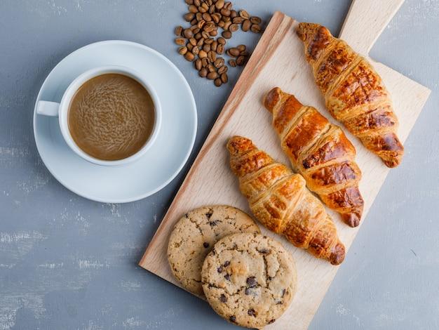 Croissants com café e feijão, biscoitos na placa de gesso e corte, plana leigos.