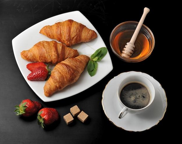 Croissants com café e mel na superfície preta