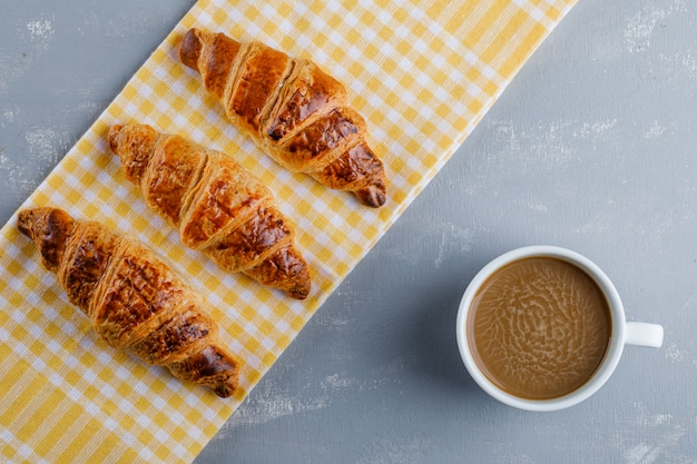 Croissants com café em gesso e toalha de cozinha, plana leigos.