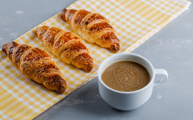 Croissants com café em gesso e toalha de cozinha,