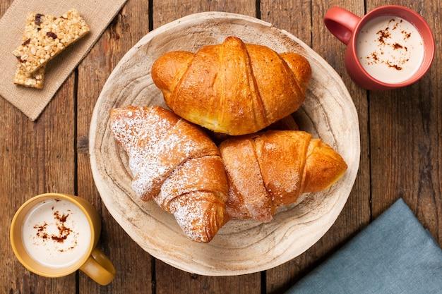 Croissants com cappuccinos na mesa de madeira