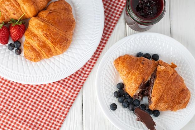 Croissants com frutas em pratos brancos na mesa de madeira