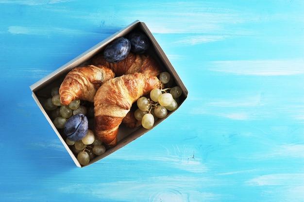 Croissants com frutas em uma caixa em um azul de madeira