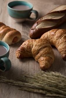 Croissants com pão e xícara de café em fundo de madeira