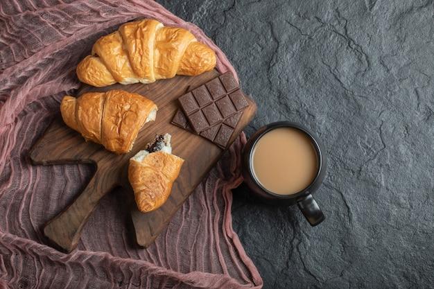 Croissants com recheio de chocolate em uma placa de madeira.