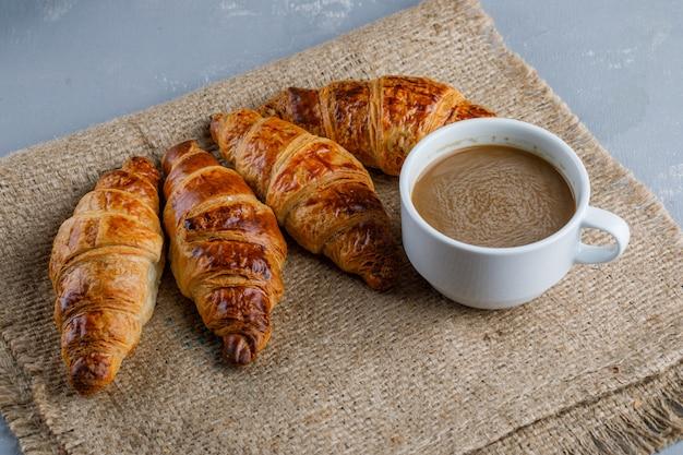 Croissants com uma xícara de café em gesso e um pedaço de saco