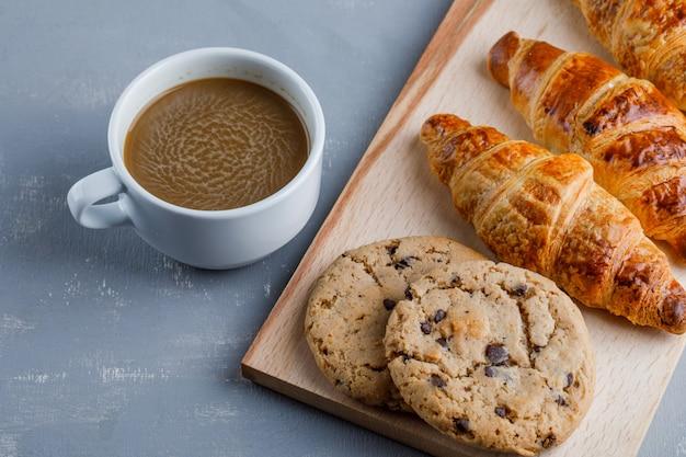 Croissants com xícara de café, biscoitos, vista de alto ângulo na placa de gesso e corte
