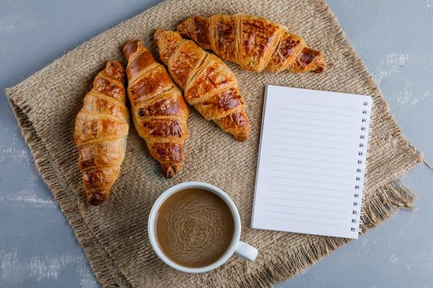 Croissants com xícara de café, caderno plano leigos em gesso e pedaço de saco