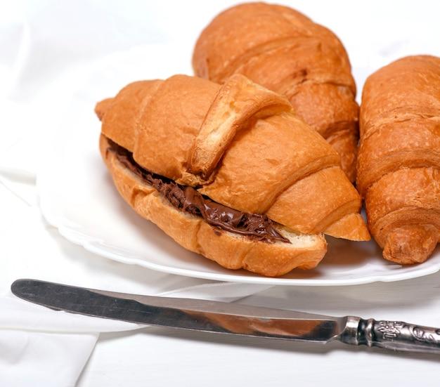 Croissants cozidos com chocolate na placa cerâmica branca