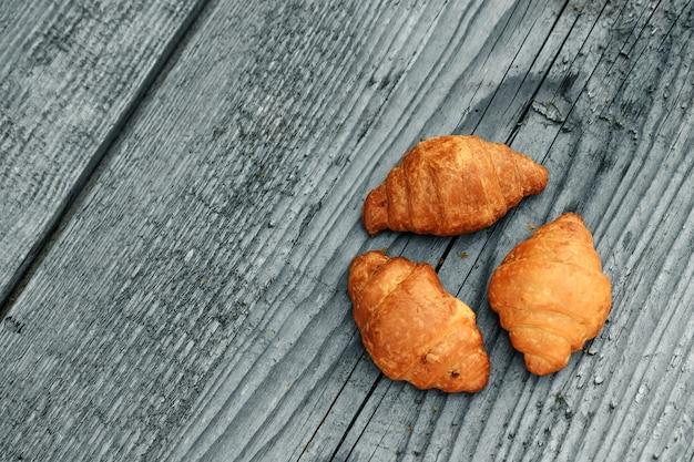 Croissants cozidos frescos em um cinza de madeira. copyspace. um bom dia, café da manhã.