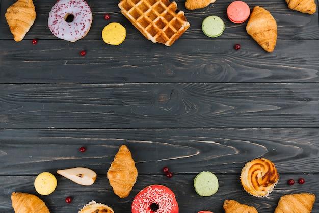 Croissants cozidos; macarrão; donuts e cupcakes no pano de fundo texturizado de madeira
