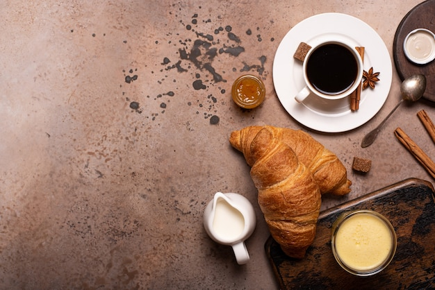 Croissants crocantes com café preto e suco de laranja em uma mesa de madeira, vista superior