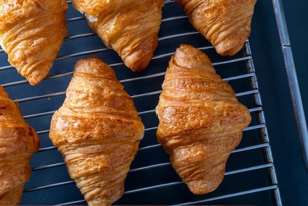 Croissants da manteiga tomados do forno em uma bandeja da grade.