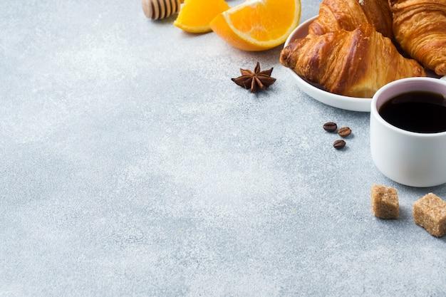 Croissants de café da manhã em um prato e uma xícara de café na mesa,