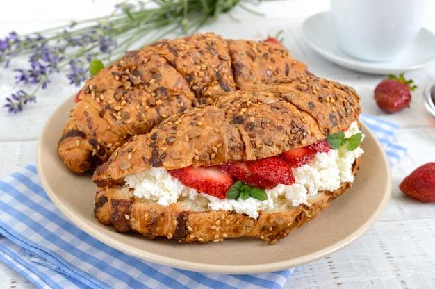 Croissants de cereais com creme de queijo e morangos frescos. café da manhã útil. nutrição apropriada. pratos tradicionais franceses.