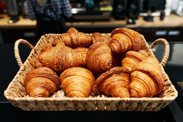 Croissants de massa folhada dobrados na cesta de vime, padaria, bolos frescos