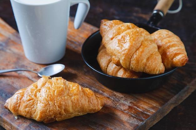 Croissants de pão de café da manhã e leite fresco na mesa de madeira