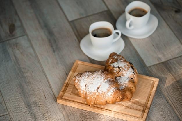 Croissants de pastelaria fresca com chocolate em uma placa de madeira e duas xícaras de café preto. café da manhã romântico
