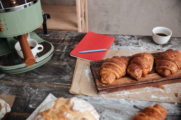 Croissants de pastelaria na mesa perto de xícara de café e notebook.