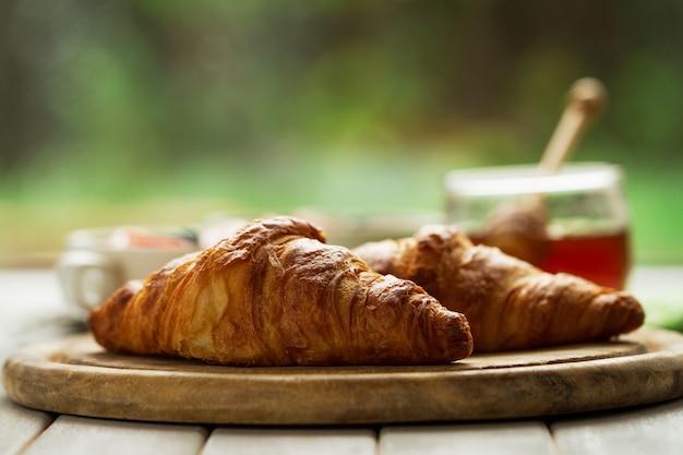 Croissants deliciosos e saborosos na placa de madeira. pequeno-almoço continental tradicional. granola com frutas e mel no fundo.
