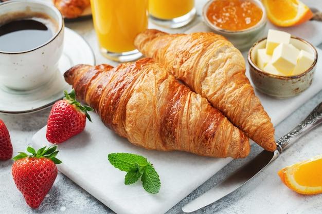 Croissants doces frescos com manteiga e geleia de laranja no café da manhã.