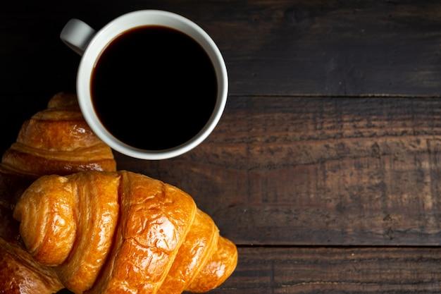Croissants e café na mesa de madeira velha.