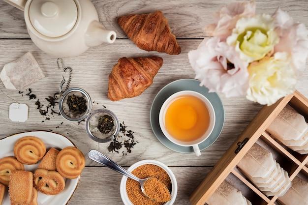 Croissants e chá em fundo de madeira