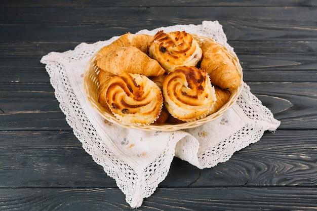 Croissants e cupcake na cesta sobre o guardanapo de renda sobre o pano de fundo de madeira