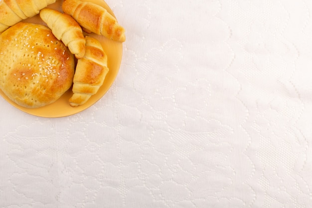 Croissants e doces de vista superior gostoso no fundo branco