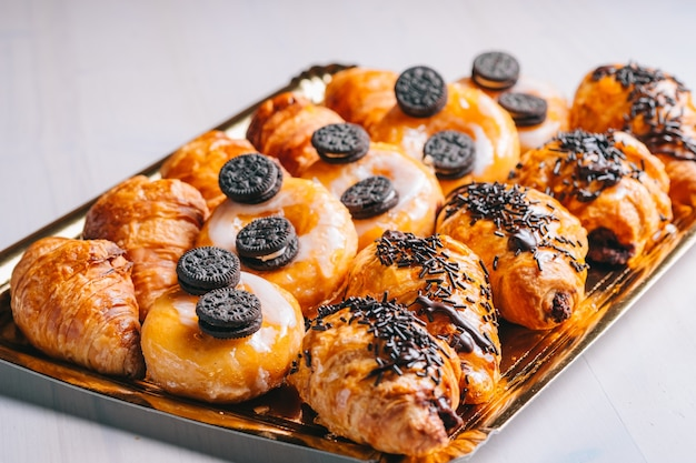 Croissants e donuts de chocolate no café da manhã, lanches doces na mesa