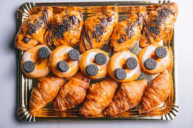 Croissants e donuts de chocolate no café da manhã vista de cima de salgadinhos doces na mesa