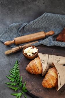 Croissants e manteiga cozidos crocantes frescos na placa de madeira
