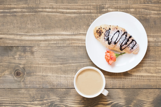 Croissants e xícara de café recentemente cozidos do chocolate na placa de madeira. vista do topo. conceito de café da manhã feminino. copie o espaço.