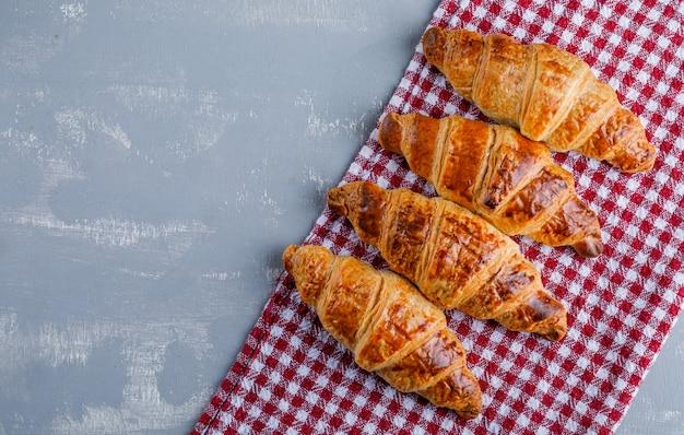 Croissants em gesso e pano de piquenique. configuração plana.