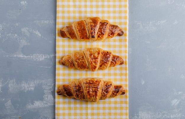 Croissants em gesso e toalha de cozinha. configuração plana.