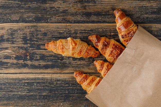 Croissants em um saco de papel em uma mesa de madeira. configuração plana.