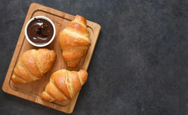 Croissants em uma placa de madeira com pasta de chocolate. vista de cima.