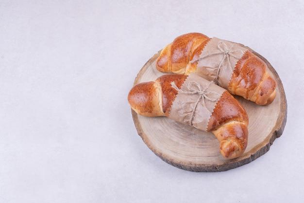 Croissants embrulhados em papel em uma travessa de madeira